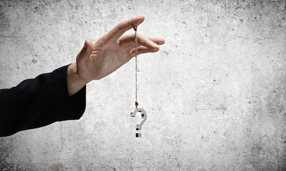 Close up of businessman hand and question sign hanging on finger