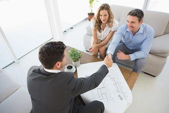 High angle view of a smiling young couple in meeting with a financial adviser at home.jpeg