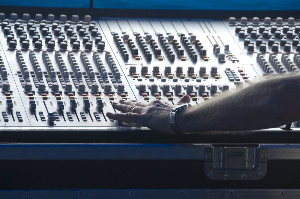 Technician's left hand makes adjustment on audio control panel in booth at outdoor concert
