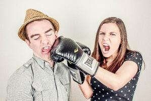 couple in a pretend fight, boxing gloves, woman hitting man with boxing gloves for fun.